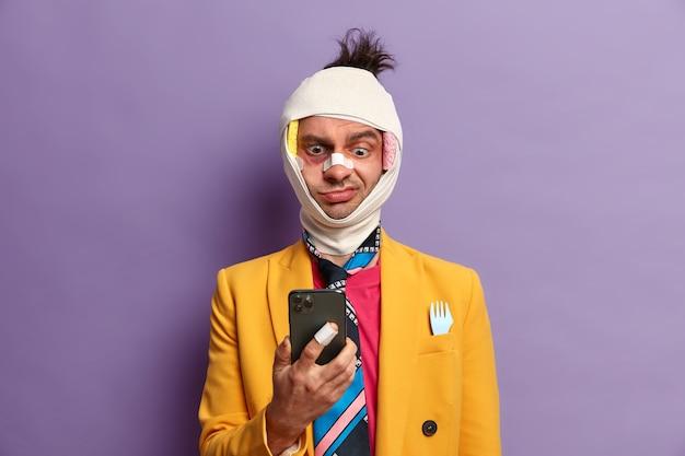 Hombre adulto alegre tiene traumatismo en la cabeza, nariz rota y hematomas debajo de los ojos