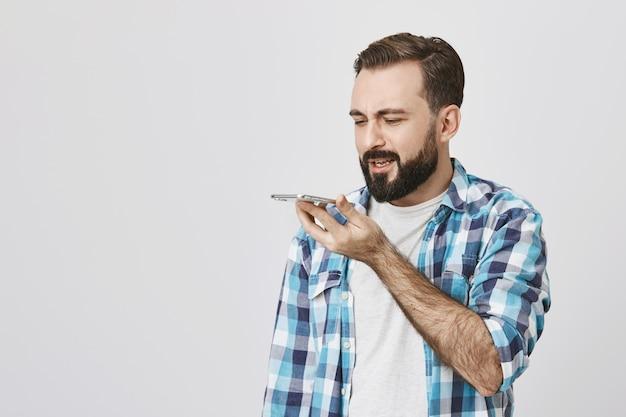 Hombre adulto con barba grabar mensaje a través del altavoz del teléfono