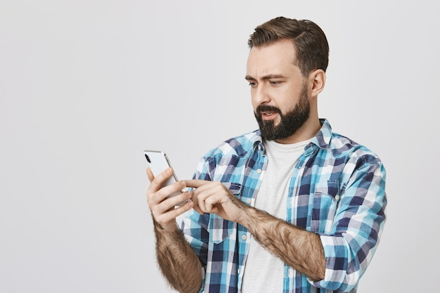 Hombre adulto con barba haciendo pedidos en línea mediante teléfono móvil