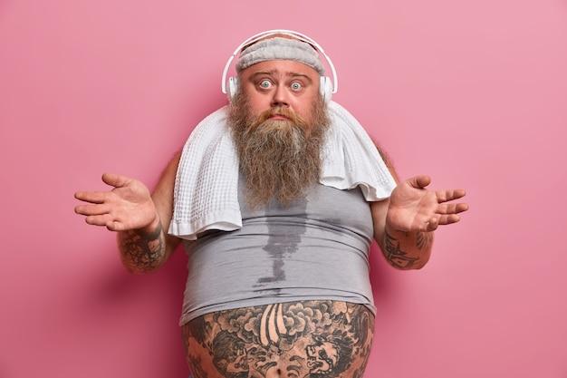 Un hombre adulto con barba y vacilante extiende las palmas de las manos y parece confundido, hace ejercicio regularmente para bajar de peso, escucha música en auriculares, usa una diadema y una camiseta de tamaño insuficiente, el vientre tatuado sobresale