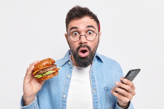 Hombre adulto barbudo hambriento come deliciosa hamburguesa sostiene teléfono móvil descubre noticias impactantes lleva camisa de mezclilla de gafas redondas