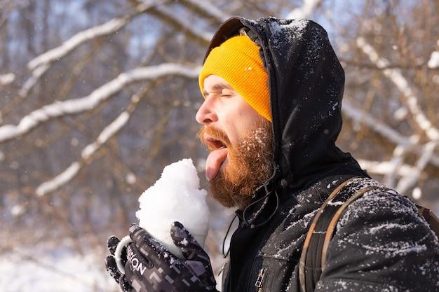 Hombre adulto brutal en un sombrero naranja brillante en un bosque nevado en un día soleado con una taza llena de nieve divirtiéndose