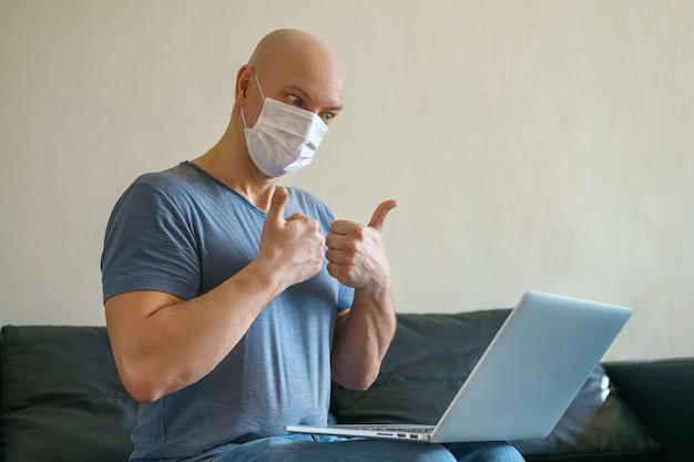 Un hombre adulto calvo se comunica en una computadora portátil en casa en el sofá, muestra un gesto con la mano. el concepto de comunicación en cuarentena.