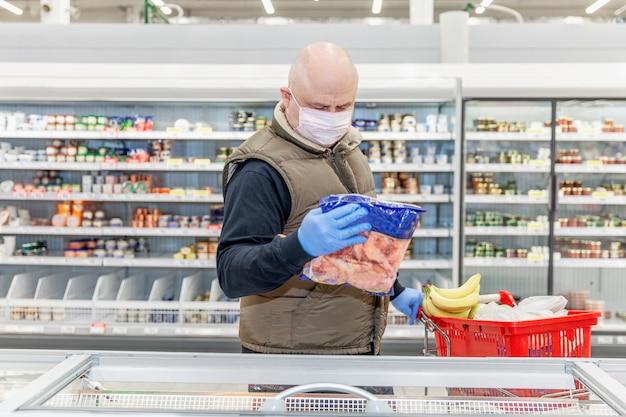 Hombre adulto calvo en una máscara médica y guantes elige alimentos congelados en un supermercado. autoaislamiento y precauciones durante la pandemia de coronavirus.