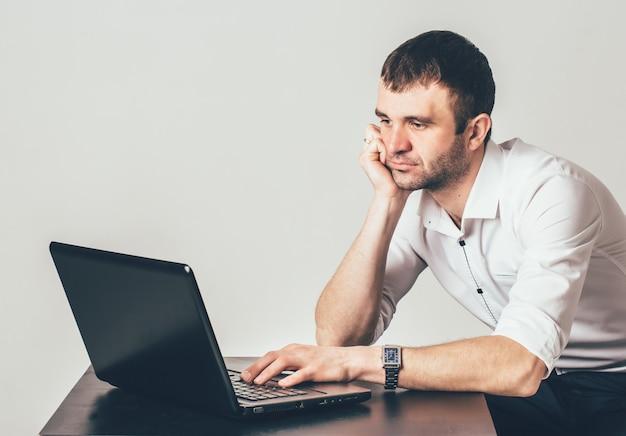El hombre adulto en la camisa blanca trabaja detrás de la computadora portátil en el cuarto. está sentado y confiando por el codo sobre la mesa y examinando la tarea.