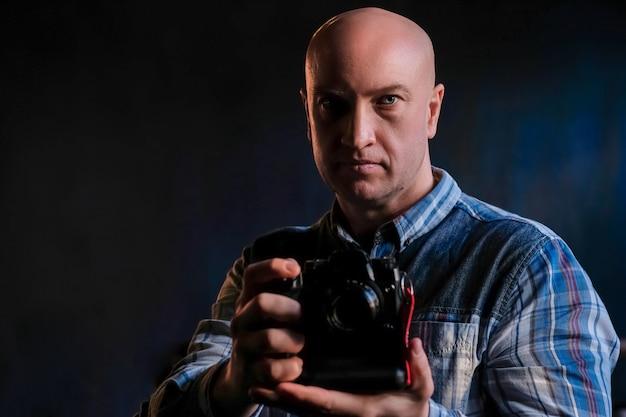 Un hombre adulto en una camisa con una cámara en sus manos.