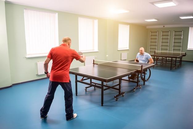 Hombre adulto discapacitado en silla de ruedas jugar al tenis de mesa con su entrenador