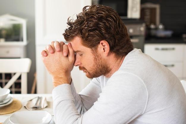 Hombre adulto emocional orando en casa