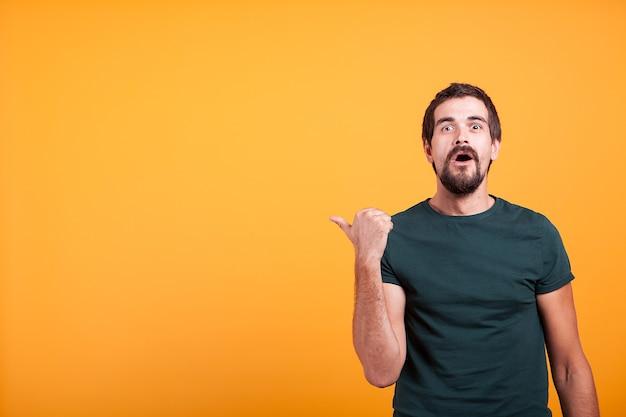 Hombre adulto emocional sorprendido apuntando al copyspace que está disponible para su texto, publicidad o promociones. concepto de asombro y entusiasmo