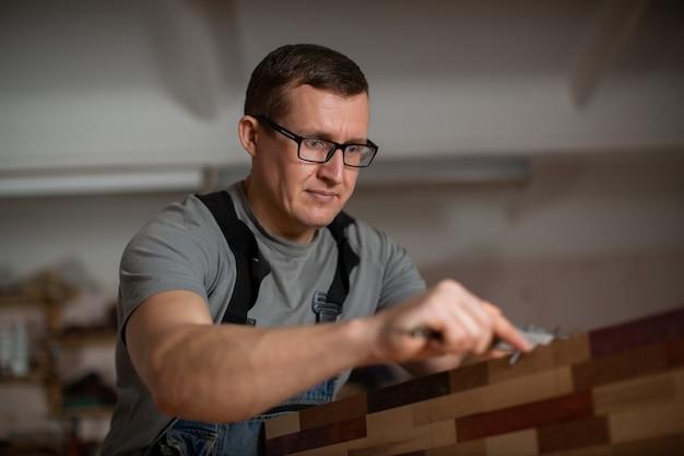 Hombre adulto con gafas maneja herramienta de carpintería de madera