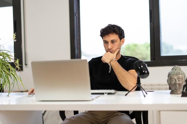 Hombre adulto graba un podcast desde casa, concepto de trabajo a domicilio digital, joven empresario
