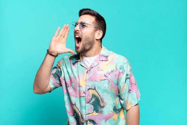 Hombre adulto guapo joven gritando fuerte y enojado para copiar el espacio en el costado, con la mano al lado de la boca