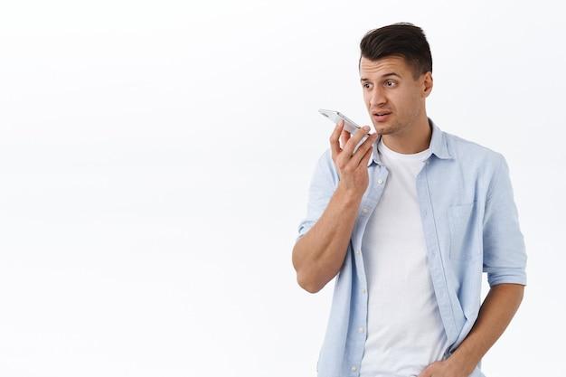 Hombre adulto guapo ocupado grabar correo de voz o mensaje de voz en el teléfono móvil, sostener el teléfono inteligente cerca de los labios lucir serio y pensativo, tener una conversación, de pie en la pared blanca