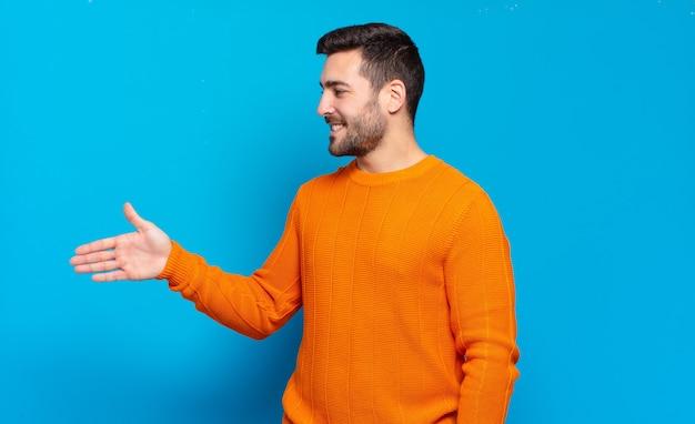 Hombre adulto guapo sonriendo, saludándote y ofreciendo un apretón de manos para cerrar un trato exitoso, concepto de cooperación