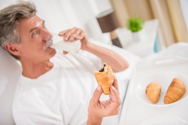 Un hombre adulto en la habitación come y descansa.