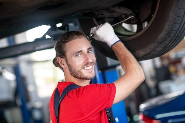 Hombre adulto joven confiado en uniforme de trabajo trabajando en coches