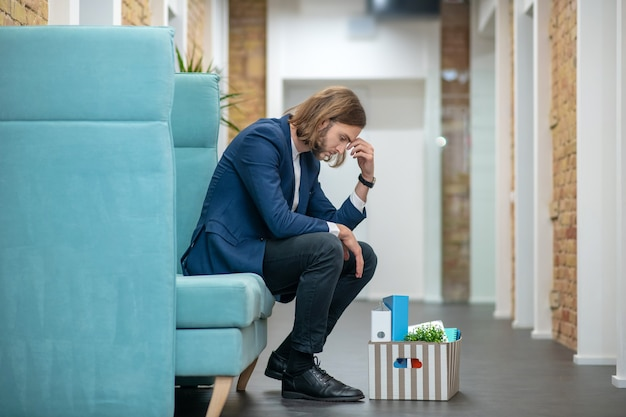 Hombre adulto joven infeliz en traje de negocios sentado en el sofá en el pasillo de la oficina triste preocupante