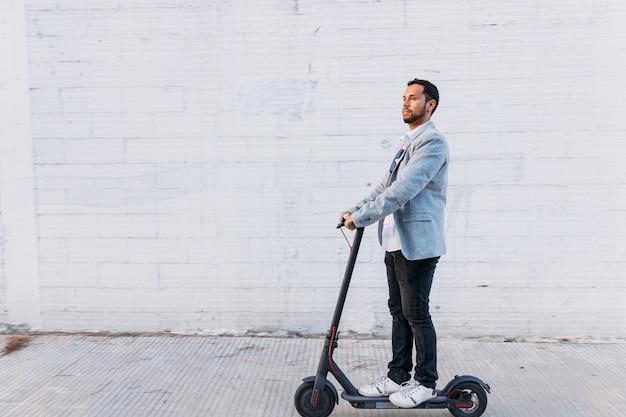 Hombre adulto latino con gafas de sol, bien vestido y scooter eléctrico en la calle con un fondo de pared blanca