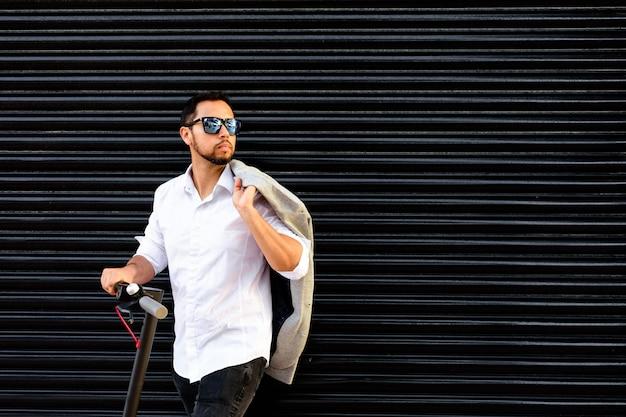 Hombre adulto latino con gafas de sol, bien vestido y scooter eléctrico hablando por su teléfono móvil en la calle con una persiana negra en el fondo