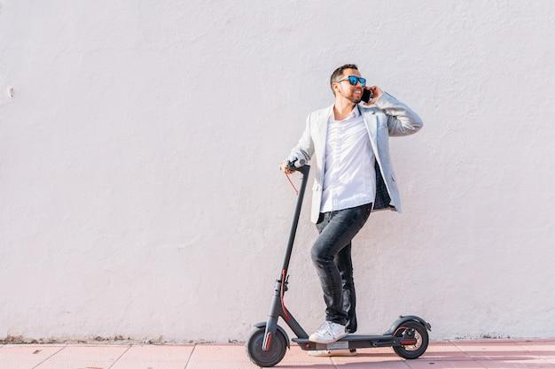 Hombre adulto latino con gafas de sol, bien vestido y scooter eléctrico hablando por su teléfono móvil sentado en la calle con un fondo de pared blanca