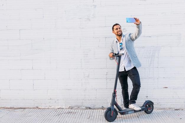 Hombre adulto latino con gafas de sol, bien vestido y scooter eléctrico tomando una selfie con su teléfono móvil en la calle con un fondo de pared blanca
