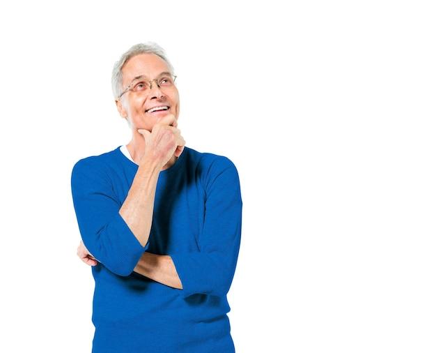 Hombre adulto mayor de pie con la mano en la barbilla sonriendo y complaciente