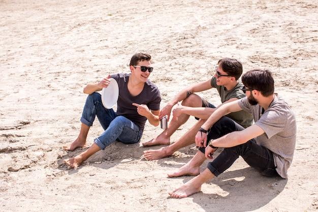 Hombre adulto ofreciendo jugar frisbee amigos sentados en la playa
