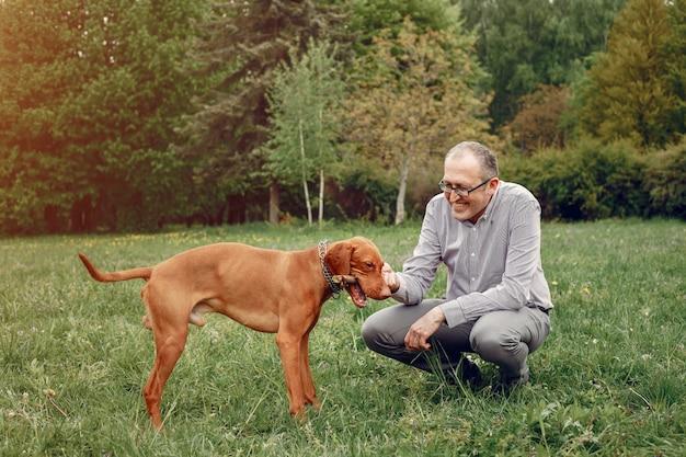 Hombre adulto en un parque de verano con un perro