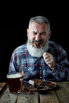 Hombre adulto de pelo gris brutal loco por el filete de mostaza y la cerveza, las vacaciones, el festival, el oktoberfest o el día de san patricio