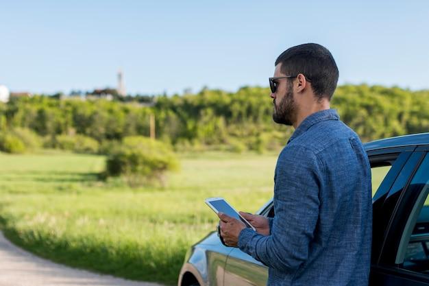 Hombre adulto de pie cerca del coche y usando tableta