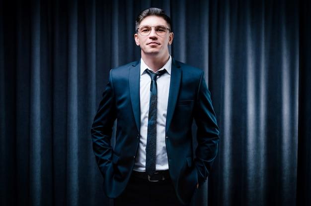 Hombre adulto está de pie en un traje contra una cortina negra