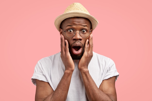 Hombre adulto de piel oscura sorprendido abre la boca con sorpresa, jadea, mira con ojos saltones, mantiene ambas manos en la cara