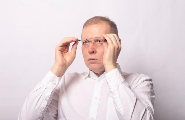 Hombre adulto poniéndose gafas. empresario con gafas sobre fondo blanco.