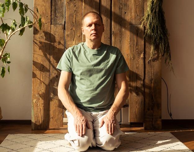 Hombre adulto en postura virasana en la estera en la acogedora casa ecológica con plantas con luz del día