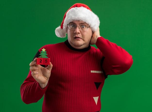 Hombre adulto preocupado con gafas y gorro de papá noel sosteniendo el juguete del árbol de navidad con fecha mirando a la cámara manteniendo la mano en la cabeza aislada sobre fondo verde