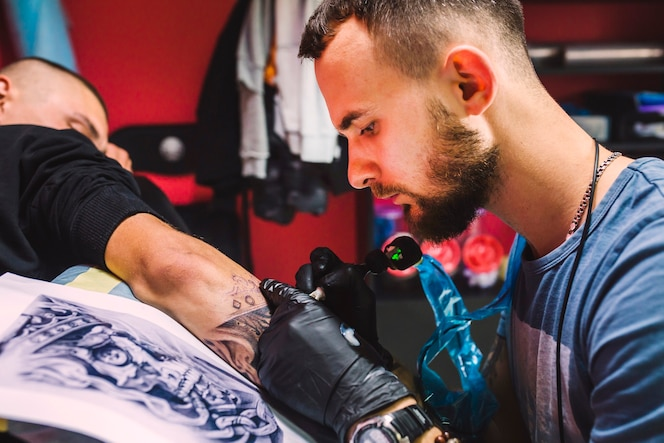 Hombre adulto que trabaja con la pluma del tatuaje en el brazo
