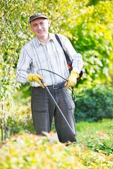 Hombre adulto rociando arbustos en el jardín
