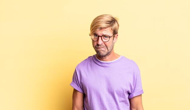 Hombre adulto rubio guapo que se siente desorientado, confundido e inseguro sobre qué opción elegir, tratando de resolver el problema