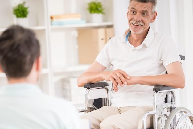 Hombre adulto sentado en casa y hablando con su padre anciano.