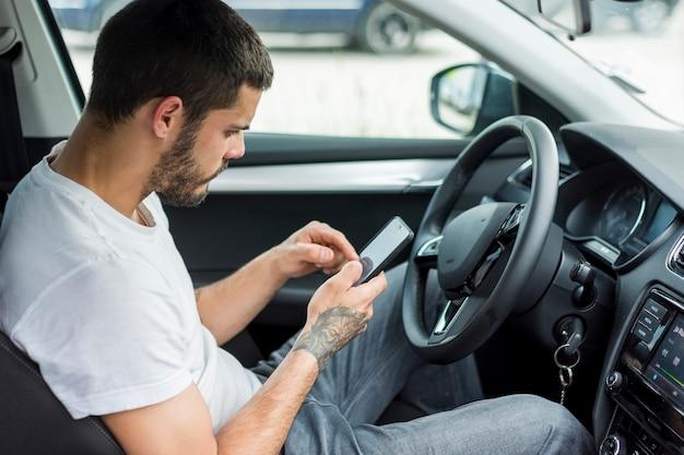 Hombre adulto sentado en el coche y usando teléfono inteligente