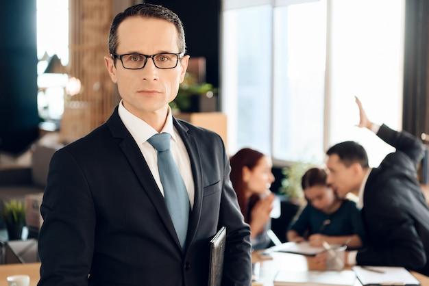 El hombre adulto serio en vidrios se coloca delante de la oficina