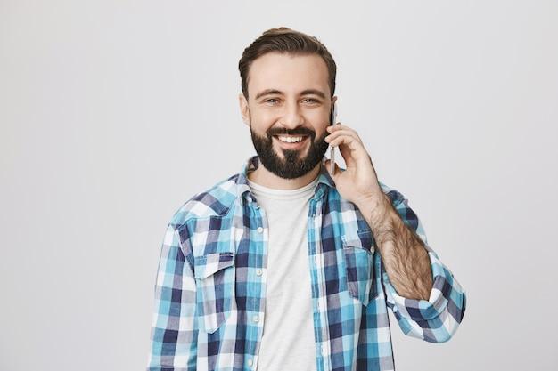 Hombre adulto sonriente amable hablando por teléfono