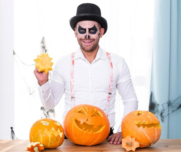 Hombre adulto sonriente con calabazas de halloween