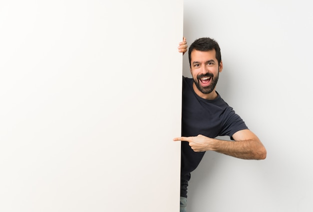 Hombre adulto sosteniendo una gran pancarta vacía y apuntando