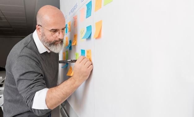 Hombre adulto tomando notas del método comercial