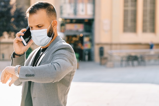 Hombre adulto en traje casual gris con máscara y distancia social