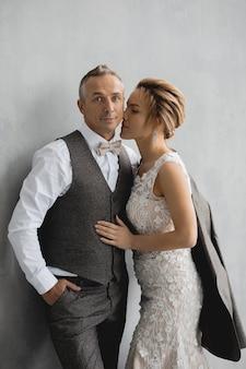 Hombre adulto con traje gris y su novia el día de la boda