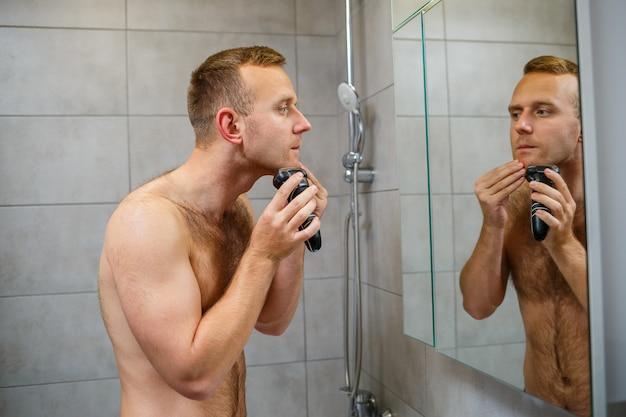 Un hombre se afeita la cara con una maquinilla de afeitar eléctrica frente a un espejo. irritación de la piel. procedimiento de baño
