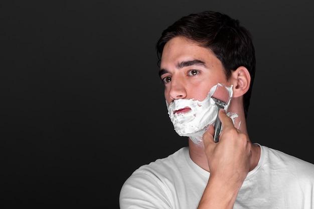 Hombre afeitado barba con maquinilla de afeitar