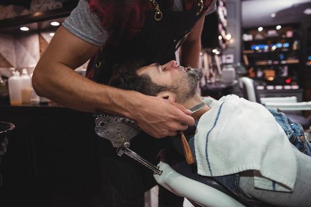 Hombre afeitado la barba con navaja